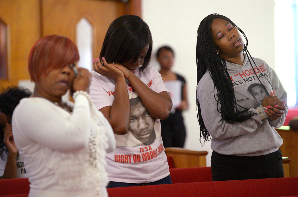 . Tammy Haynes, left, Whitney Tillman, center, and Crystal Haynes react during a sermon at a youth service at the St. Paul Missionary Baptist Church in Sanford, Fla., Sunday, July 14, 2013.  Many in the congregation wore shirts in support of Trayvon Martin following the acquittal of  George Zimmerman, who had been charged in the 2012 shooting death of  Martin.  (AP Photo/Phelan M. Ebenhack)