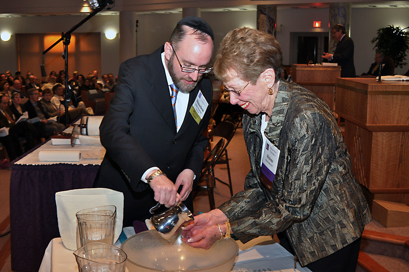 Rabbi Youlus helps Helene Schrott wash her hands before filling in the fifth-to-last letter (photo by Sam Backman)