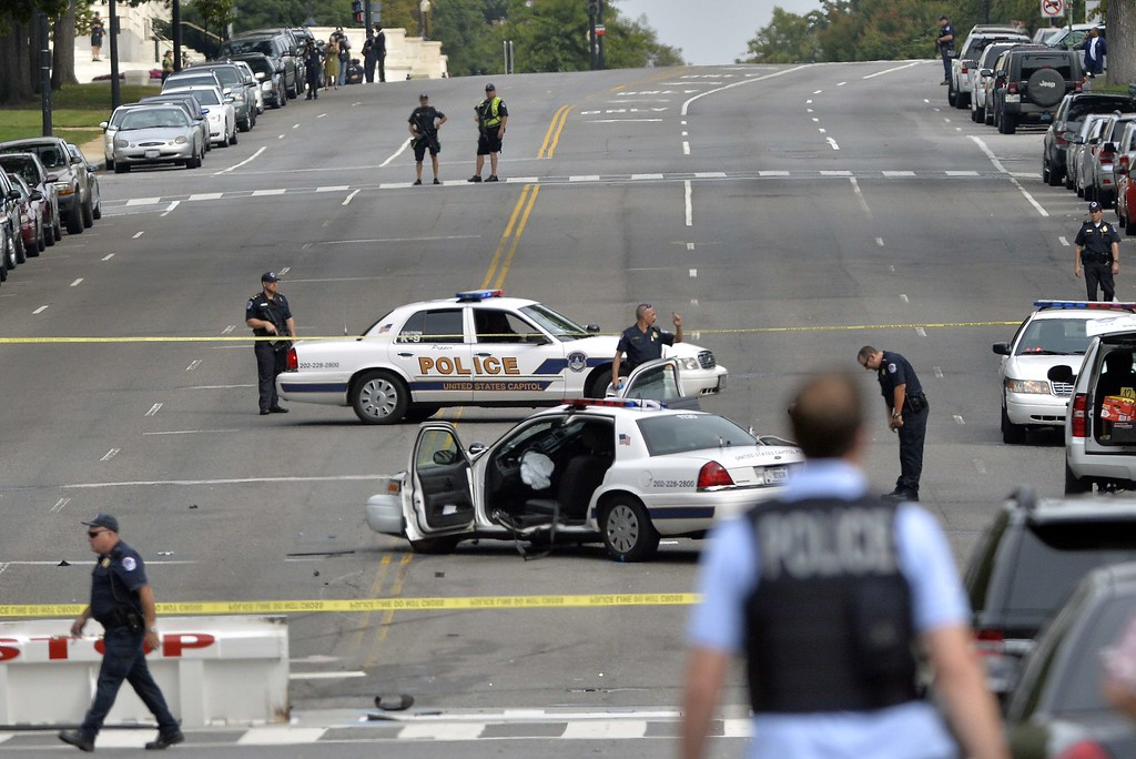 """. A police cruiser is wrecked after shots fired were reported near 2nd Street NW and Constitution Avenue on Capitol Hill in Washington, DC, on October 3, 2013.  The US Capitol was placed on security lockdown Thursday after shots were fired outside the complex, senators said. \""""Shots fired outside the Capitol. We are in temporary lock down,\"""" Senator Claire McCaskill said on Twitter. Police were seen running within the Capitol building and outside as vehicles swarmed to the scene. AFP Photo/Jewel SAMAD/AFP/Getty Images"""