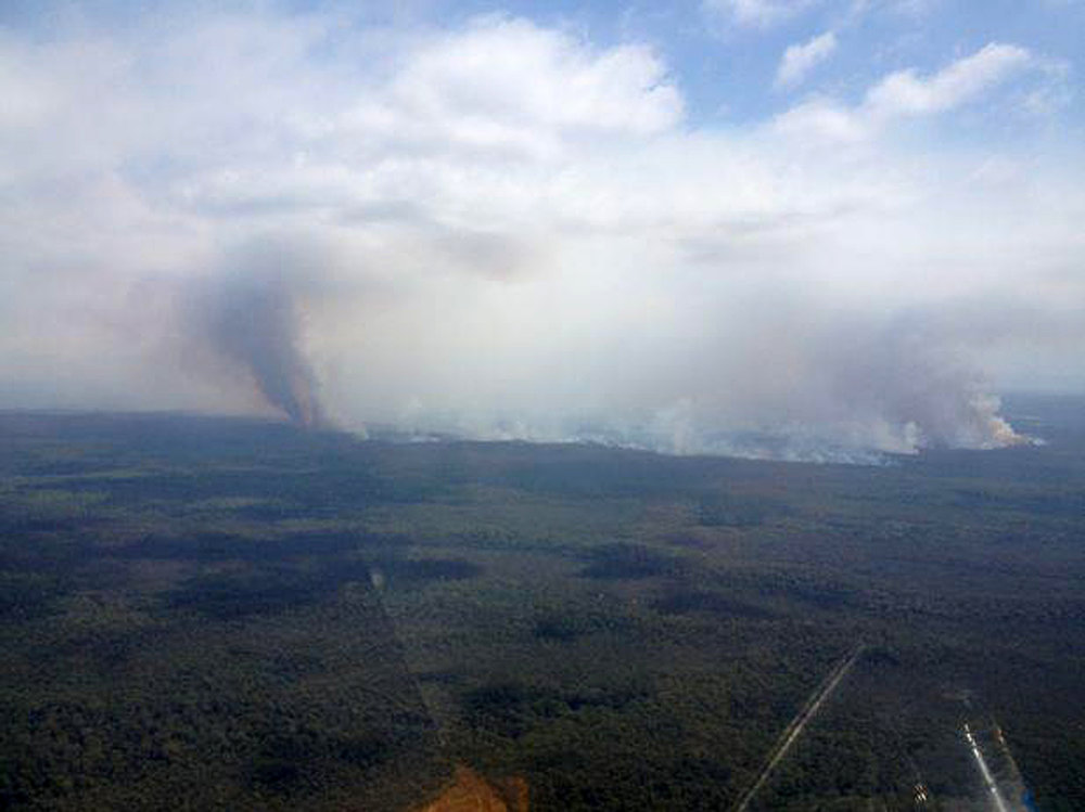 . In this aerial photo provided by the New South Wales Rural Fire Service, plumes of smoke rises from a fire near Sussex Inlet, Australia, Wednesday, Jan. 9, 2013. Temperatures cooled from record highs across much of southern Australia on Wednesday, reducing the danger from scores of wildfires that have blazed for days.  (AP Photo/NSW Rural Fire Service)