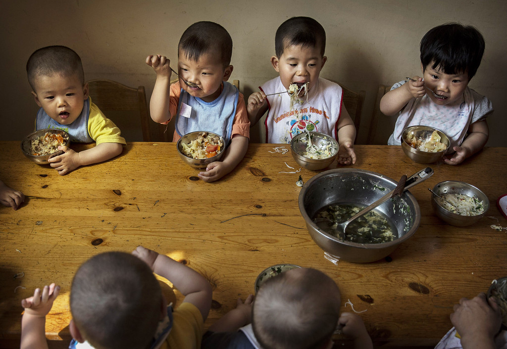 . Young orphaned Chinese children eat a meal during feeding at a foster care center on April 2, 2014 in Beijing, China.  (Photo by Kevin Frayer/Getty Images)