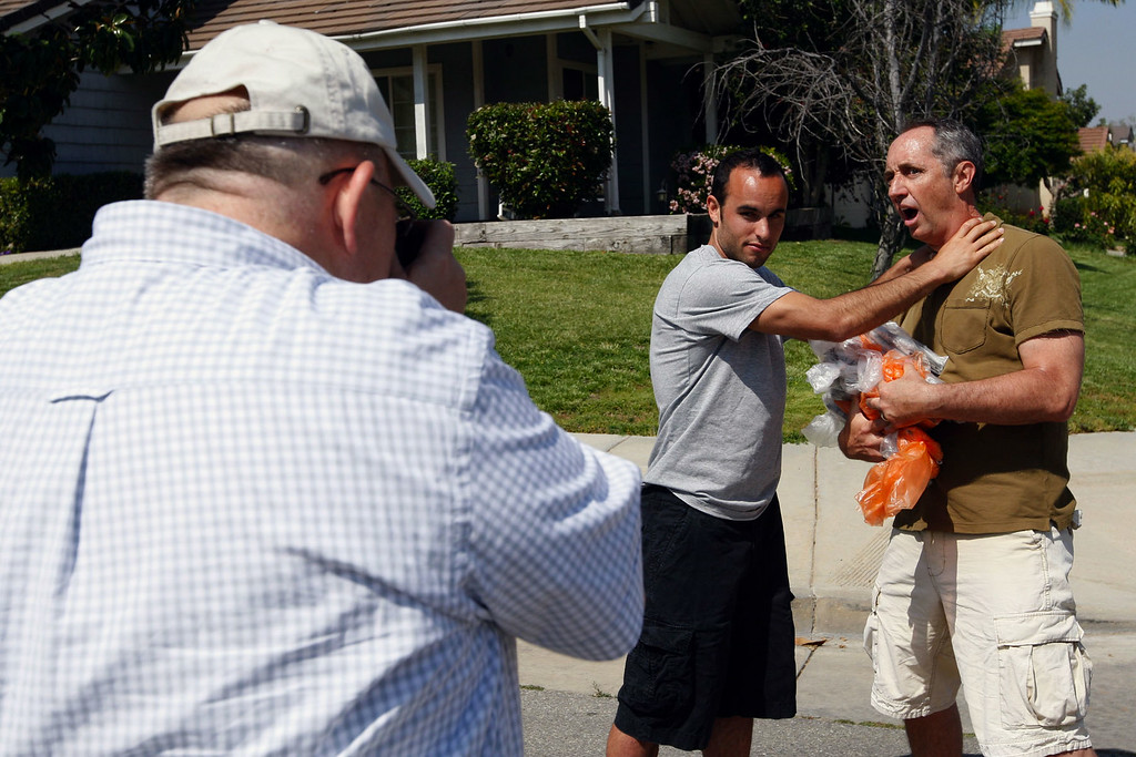 """. Supervising Producer Mike Kostel, left, takes a photograph of Landon Donovan pretending to choke Rick Reilly after filming a segment for ESPN\'s \""""Home Coming with Rick Reilly\"""" in Redlands Monday, April 19, 2010. (Staff file photo/Redlands Daily Facts)"""