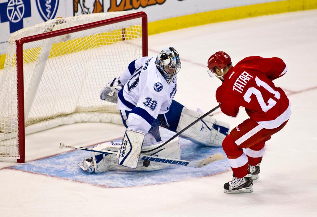 . Tampa Bay Lightning goalie Ben Bishop (30) blocks a shot by Detroit Red Wings forward Tomas Tatar (21), of Slovakia, during the shootout in an NHL hockey game in Detroit, Sunday, Nov. 9, 2014. Tampa Bay won 4-3. (AP Photo/Tony Ding)