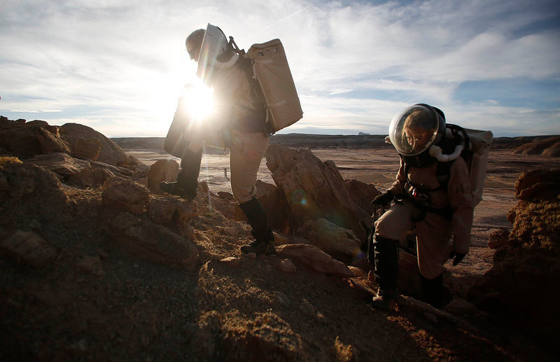 . Melissa Battler (L), a geologist and commander of the Crew 125 EuroMoonMars B mission, and Csilla Orgel, a geologist, climb a rock formation to collect geologic samples for study at the Mars Desert Research Station (MDRS) in the Utah desert March 2, 2013.  REUTERS/Jim Urquhart