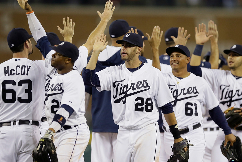 . Detroit Tigers outfielders Rajai Davis (20), J.D. Martinez (28) and Ezequiel Carrera  (61) greet teammates after their 11-5 win over the Colorado Rockies in an interleague baseball game, Saturday, Aug. 2, 2014, in Detroit. (AP Photo/Carlos Osorio)