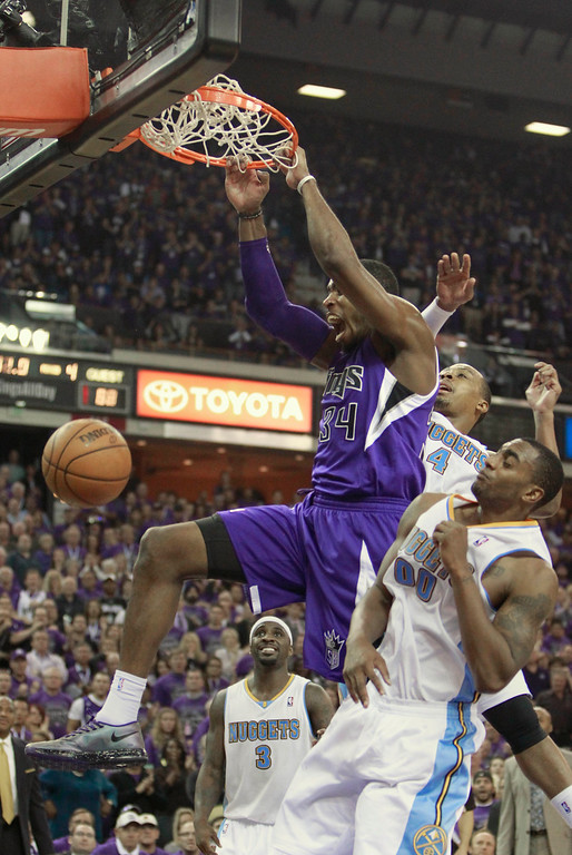 . Sacramento Kings forward Jason Thompson, center, hangs on the rim after scoring the winning basket between Denver Nuggets\' Randy Foye, center and Darrell Arthur during closing moments of an NBA basketball game in Sacramento, Calif., Wednesday, Oct. 30, 2013. The Kings won 90-88. (AP Photo/Rich Pedroncelli)