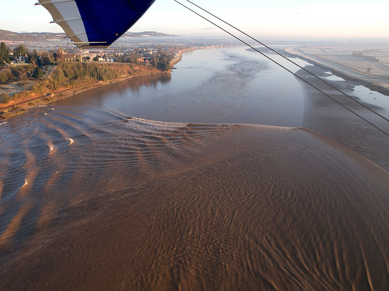To witness the Severn Bore from the air is like nothing else. One can really appreciate the topography of the river as it channels the huge wave down the estuary and into the narrow sections upstream. The wave takes on many shapes and characteristics that just cannot be appreciated from the ground. It is a great vantage point to see the gravity waves. Most people perceive the bore to be a single wave. Check the images and dispel that myth. The wing was deliberate. Olympus E3, 12-60mm SWD