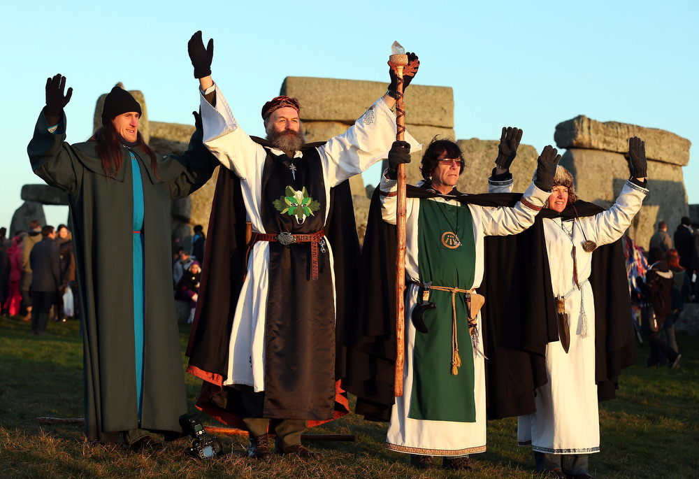 Description of . Druids react as the sun rises, as druids, pagans and revellers take part in a winter solstice ceremony at Stonehenge on December 21, 2012 in Wiltshire, England. Predictions that the world will end today as it marks the end of a 5,125-year-long cycle in the ancient Maya calendar, encouraged a larger than normal crowd to gather at the famous historic stone circle to celebrate the sunrise closest to the Winter Solstice, the shortest day of the year.  (Photo by Matt Cardy/Getty Images)