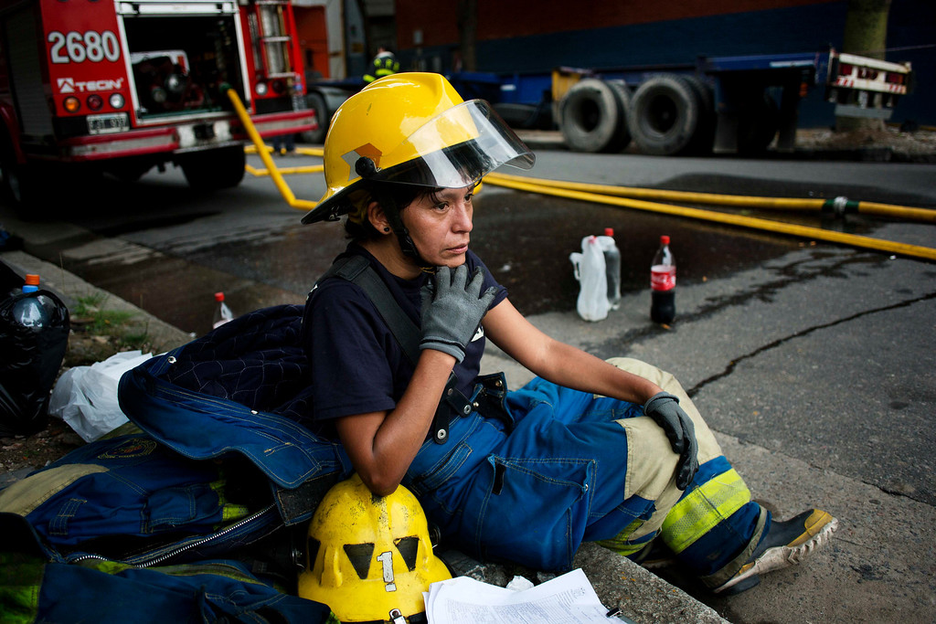 . Firefighter Guadalupe Gonzalez rests after working to extinguish a fire at the Iron Mountain warehouse in Buenos Aires, Argentina, Wednesday, Feb. 5, 2014. (AP Photo/Rodrigo Abd)