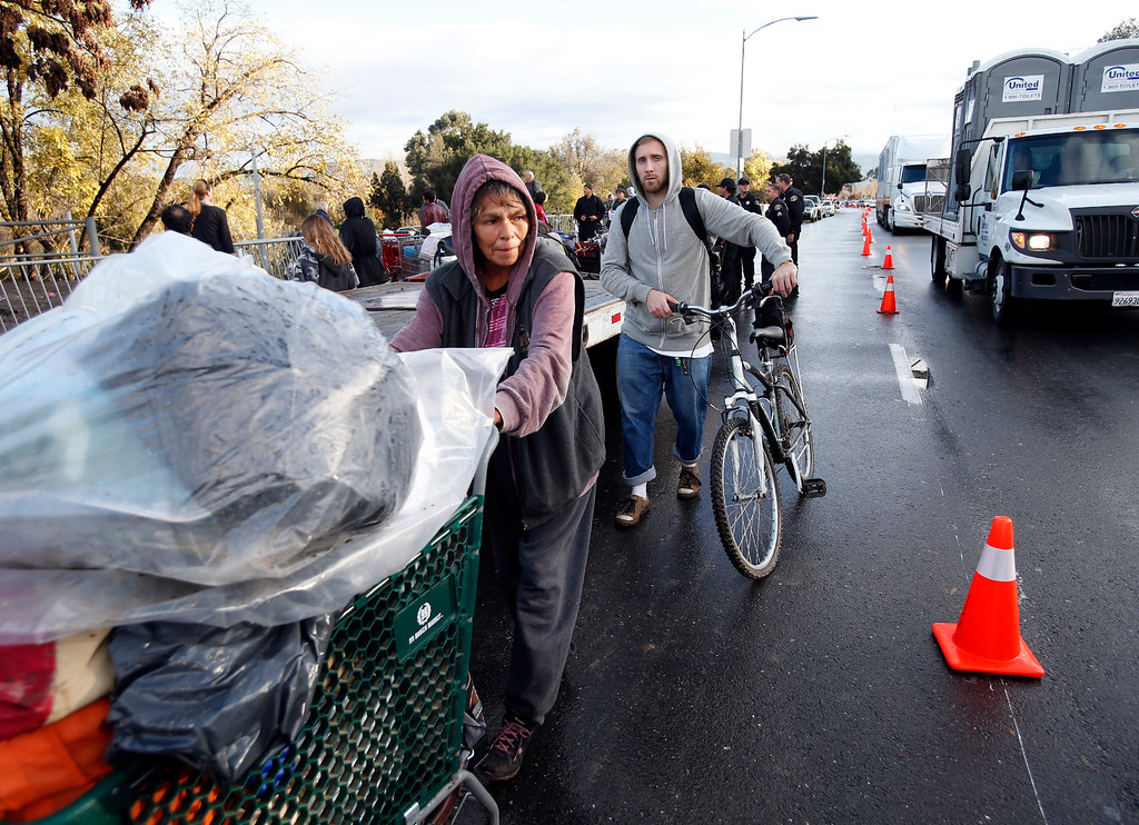. Eva Marie Martinez, 63, a longtime resident of The Jungle homeless camp, pushes her cart down Story Road after being evicted Thursday, Dec. 4, 2014, from the site along the Coyote Creek in San Jose, Calif. (Karl Mondon/Bay Area News Group)