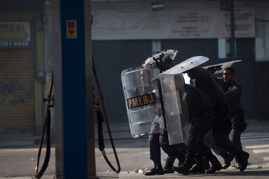 . Police officers protect themselves from missiles thrown by protesters near the area recently occupied by squatters in Rio de Janeiro, Brazil, Friday, April 11, 2014. Squatters in Rio de Janeiro are clashing with police after a Brazilian court ordered that 5,000 people be evicted from abandoned buildings of a telecommunications company. Officers have used tear gas and stun grenades to try to disperse the families. (AP Photo/Felipe Dana)