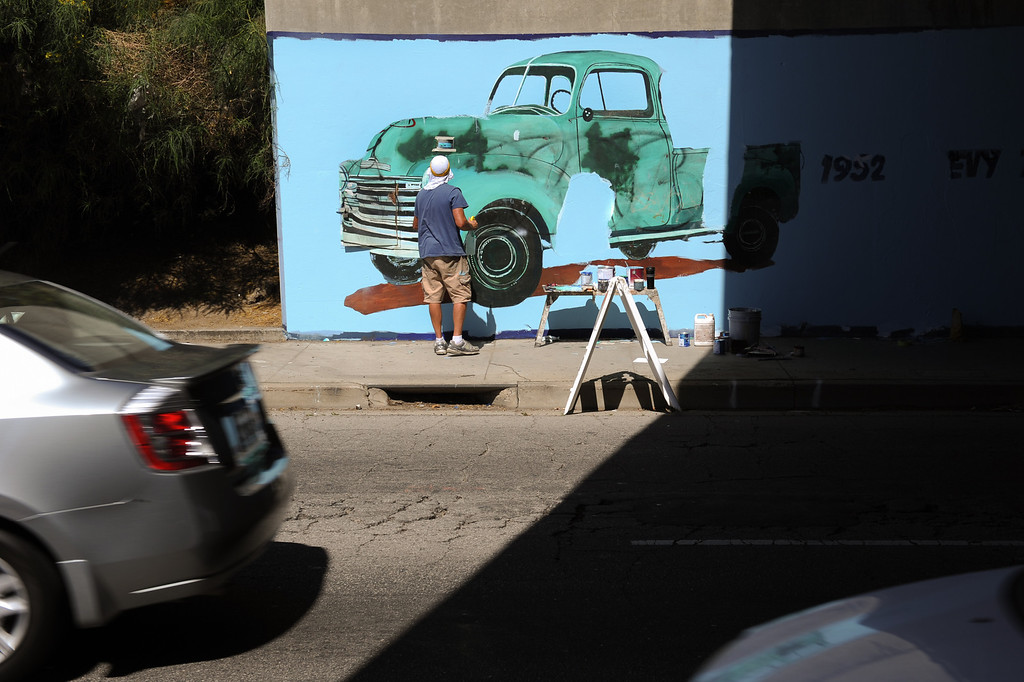 """. Cars drive along Van Nuys Boulevard as Jeff Lingle paints during the restoration of the mural \""""Panorama: G.M. Recollections from the Past,\"""" on Van Nuys Boulevard in Panorama City, Thursday, June 20, 2013. The original mural was painted by Alfredo Diaz Flores in 1998 and pays homage to the General Motors plant that used to be near the mural site. (Michael Owen Baker/Staff Photographer)"""