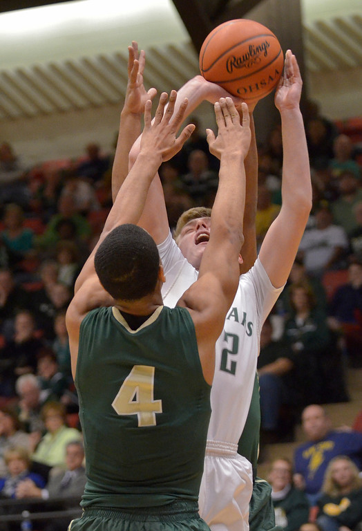 . Jeff Forman/JForman@News-Herald.com Connor Fitzgerald shoots over Irish defender Josh Williams in the first half of the Cougars\'  68-52 Division II regional semifinal loss March 13 to St. Vincent St. Mary at the Canton Civic Center.