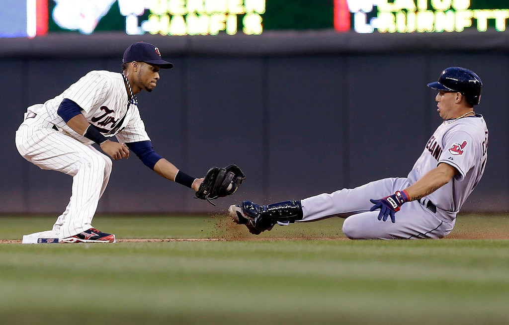. Cleveland Indians\' Asdrubal Cabrera, right, slides into the waiting tag from Minnesota Twins shortstop Pedro Florimon as he attempted to stretch a single into a double. (AP Photo/Jim Mone)