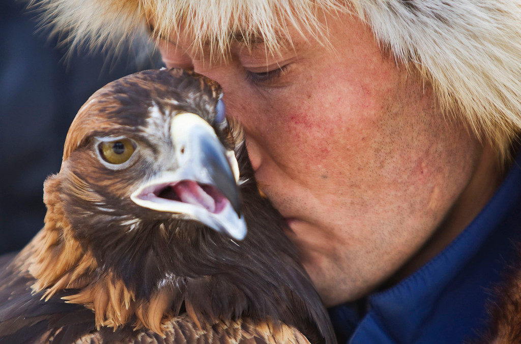 . A Kazakh hunter whispers to his tamed golden eagle during an annual hunting competition in Chengelsy Gorge, some 150 km (93 miles) east of Almaty February 23, 2013.  REUTERS/Shamil Zhumatov