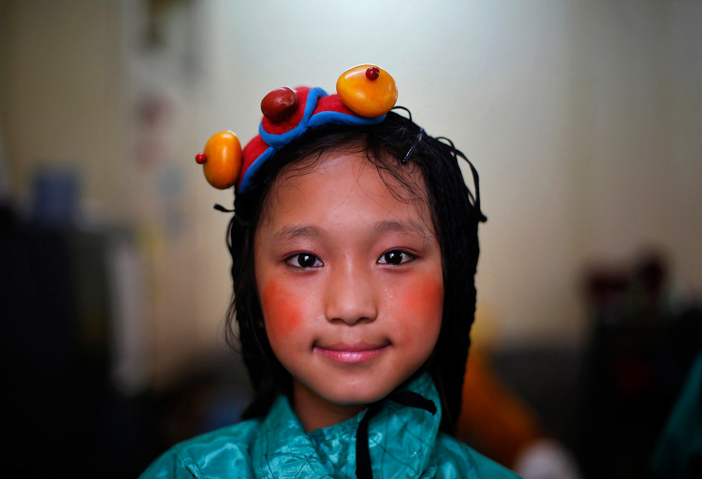 . A Tibetan exile poses for a picture after her performance during celebrations of the 78th birthday of exiled Tibetan spiritual leader Dalai Lama at Majnu Ka Tila, a Tibetan refugee camp in New Delhi July 6, 2013. REUTERS/Adnan Abidi