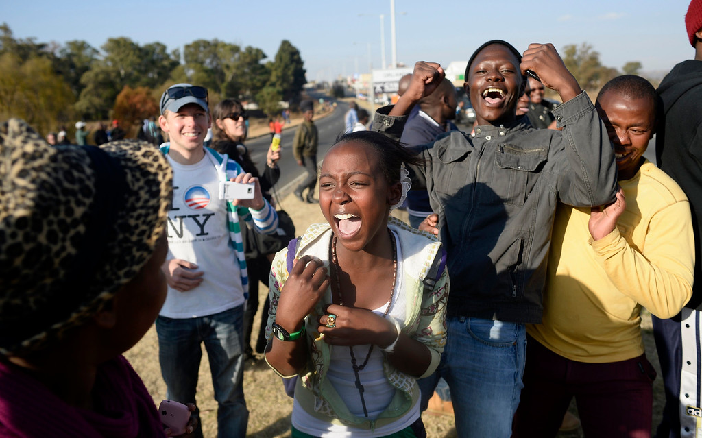 . Bystanders cheer after catching a brief glimpse of U.S. President Barack Obama as he arrives at the University of Johannesburg in Soweto, June 29, 2013.  REUTERS/Dylan Martinez