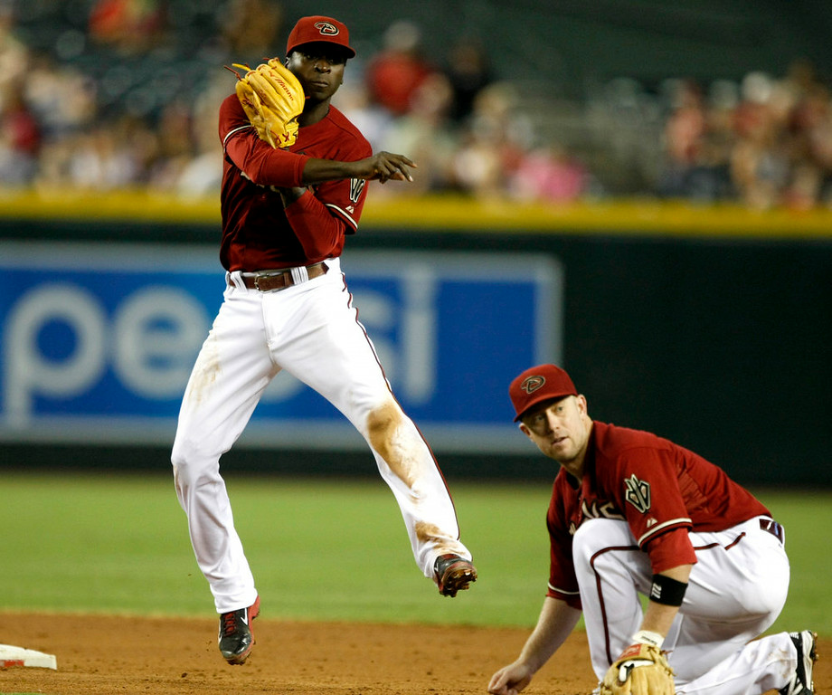 . Arizona Diamondbacks shortstop Didi Gregorius, left, turns the double play while avoiding second baseman Aaron Hill, right, in the fourth inning during a baseball game against the Colorado Rockies, Sunday, Aug. 10, 2014, in Phoenix. (AP Photo/Rick Scuteri)