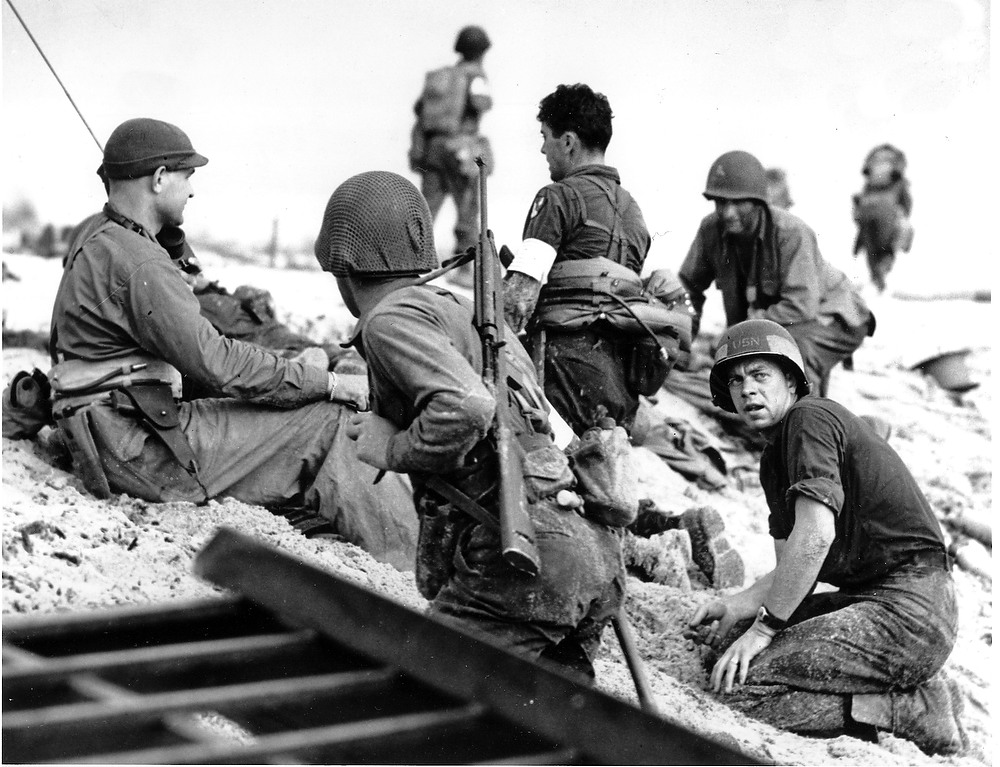 Description of . A first wave beach battalion Ducks lays low under the fire of Nazi guns on the beach of southern France on D-Day, June 6, 1944 during World War II.  One invader operates a walkie talkie radio directing other landing craft to the safest spots for unloading their parties of fighting men.   (AP Photo)