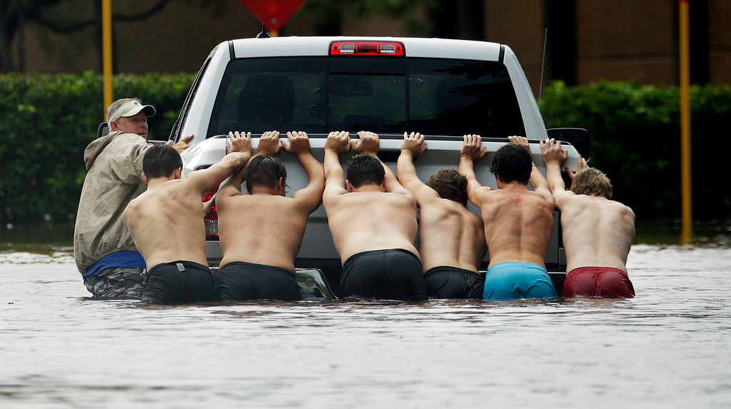 . People push a stalled pickup through a flooded street in Houston, after Tropical Storm Harvey dumped heavy rains, Sunday, Aug. 27, 2017. The remnants of Harvey sent devastating floods pouring into Houston on Sunday as rising water chased thousands of people to rooftops or higher ground. (AP Photo/Charlie Riedel)