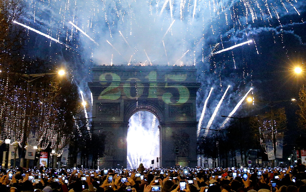 . Revelers photograph fireworks over the Arc de Triomphe as they celebrate the New Year\'s Eve on the Champs Elysees avenue in Paris, France, Thursday, Jan. 1, 2015. (AP Photo/Christophe Ena)