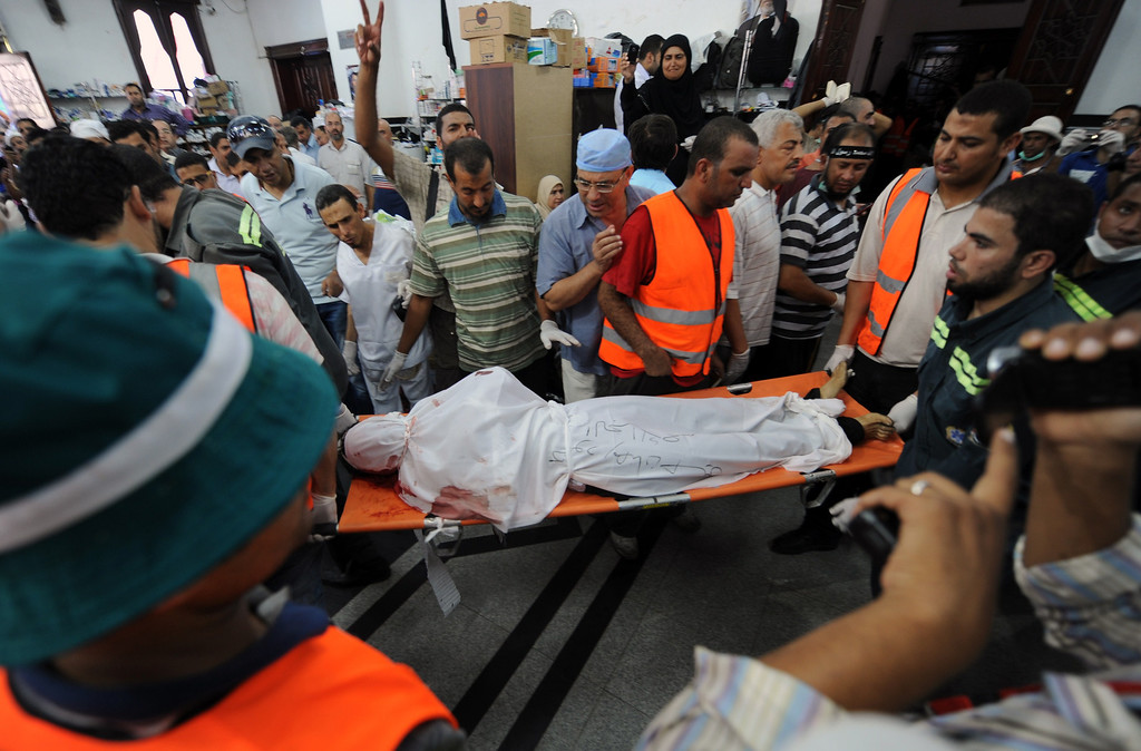 """. The body of a Muslim Brotherhood protester, shot dead in the Egyptian capital after violence erupted the night before, is evacuated as mourners watch inside a field hospital in Cairo on July 27, 2013. The bloodshed came hours after the military-backed interior minister, Mohammed Ibrahim, warned a long-running sit-in at Cairo\'s Rabaa al-Adawiya mosque by Morsi loyalists would be ended \""""in the framework of the law\"""". FAYEZ NURELDINE/AFP/Getty Images"""