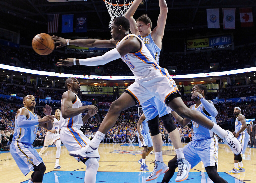 . Oklahoma City Thunder guard Reggie Jackson (15) passes from under the basket in front of Denver Nuggets center Timofey Mozqov (25) in the first quarter of an NBA basketball game in Oklahoma City, Monday, March 24, 2014. (AP Photo/Sue Ogrocki)