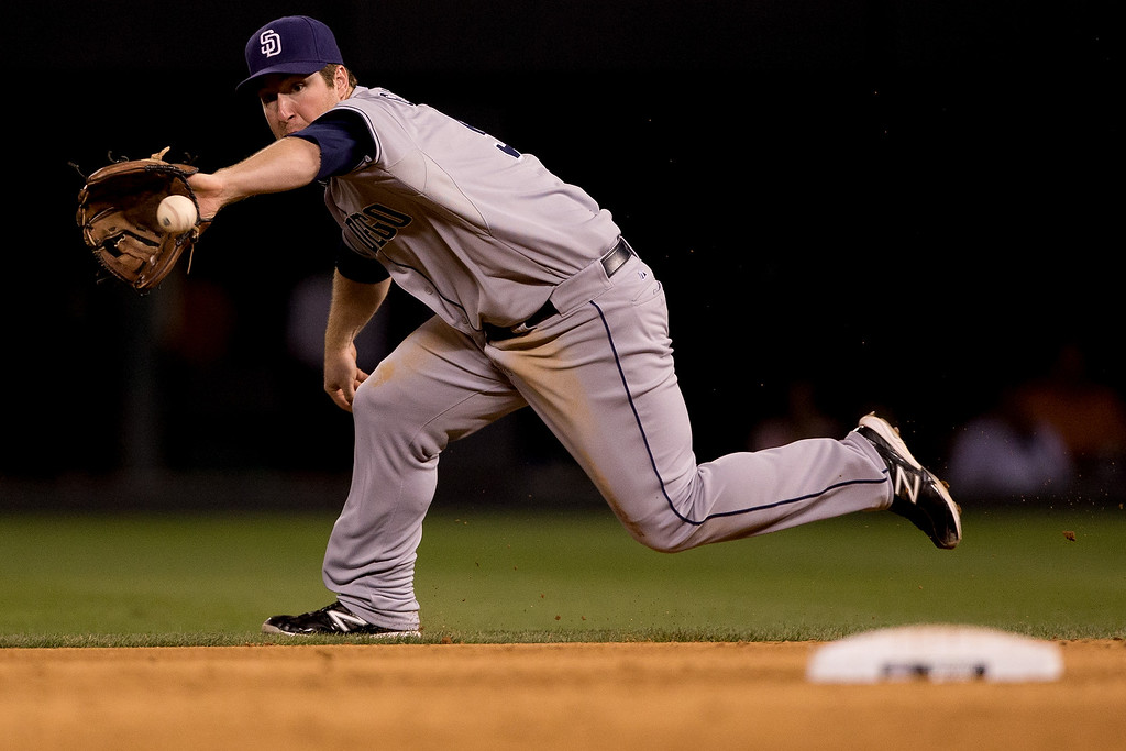. Second baseman Jedd Gyorko #9 of the San Diego Padres runs down a ground ball for an out against DJ LeMahieu of the Colorado Rockies for the second out of the sixth inning at Coors Field on August 13, 2013 in Denver, Colorado.  The Padres defeated the Rockies 7-5.  (Photo by Justin Edmonds/Getty Images)