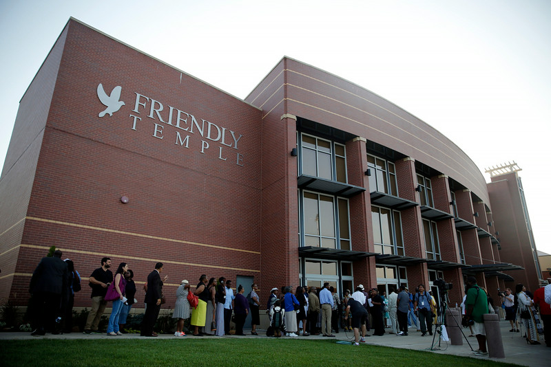 . People begin to line up to attend the funeral for Michael Brown, Monday, Aug. 25, 2014, in St. Louis. Brown, who is black, was unarmed when he was shot Aug. 9 by Officer Darren Wilson, who is white. A grand jury is considering evidence in the case and a federal investigation is also underway. (AP Photo/Jeff Roberson)