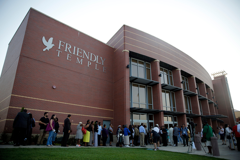 Description of . People begin to line up to attend the funeral for Michael Brown, Monday, Aug. 25, 2014, in St. Louis. Brown, who is black, was unarmed when he was shot Aug. 9 by Officer Darren Wilson, who is white. A grand jury is considering evidence in the case and a federal investigation is also underway. (AP Photo/Jeff Roberson)