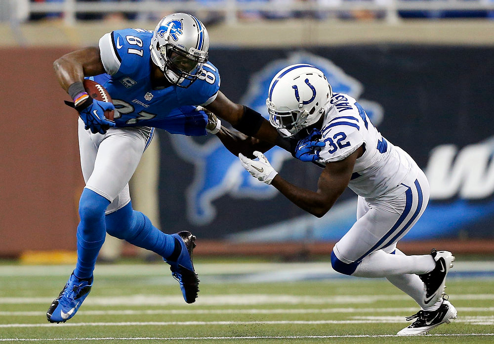 Description of . Detroit Lions wide receiver Calvin Johnson (81) is pulled by Indianapolis Colts cornerback Cassius Vaughn (32) during the first quarter of an NFL football game at Ford Field in Detroit, Sunday, Dec. 2, 2012. (AP Photo/Rick Osentoski)