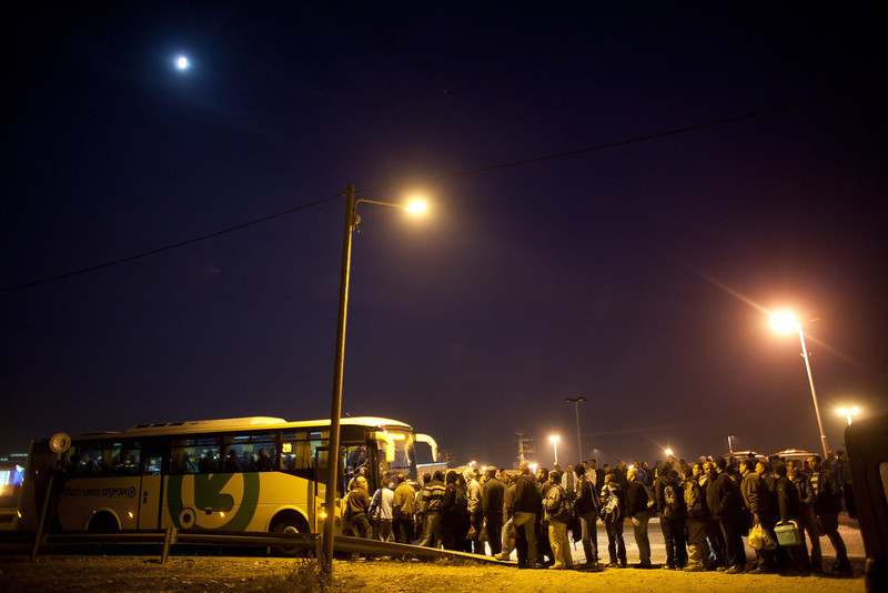 . Palestinians wait to board a bus as a new line is made available by Israel to take Palestinian laborers from the Israeli army crossing of Eyal, near the West Bank town of Qalqilya, into Israeli cities on March 4, 2013. The new line service to ferry Palestinian workers from the West Bank to Israel, encouraging them to use it instead of traveling with Israeli settlers on a similar route.  (Photo by Uriel Sinai/Getty Images)