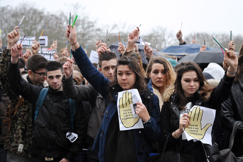 . Students hold pens and signs reading \'Don\'t touch to my freedom of speech\'\' in La Rochelle, on January 8, 2015, as they gathered to pay tribute to the twelve people killed the day before in an attack by two armed gunmen on the offices of French satirical newspaper Charlie Hebdo in Paris. A huge manhunt for two brothers suspected of massacring 12 people in an Islamist attack at a satirical French weekly zeroed in on a northern town Thursday after the discovery of one of the getaway cars.  As thousands of police tightened their net, the country marked a rare national day of mourning for Wednesday\'s bloodbath at Charlie Hebdo magazine in Paris, the worst terrorist attack in France for half a century. AFP PHOTO / XAVIER LEOTY/AFP/Getty Images