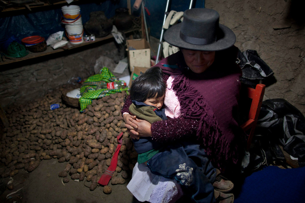 . A child sleeps in the arms of a woman in Chaca, Peru. The woman arrived in the village to attend a mass burial of villagers slain by insurgents nearly three decades ago by Shining Path militants in retaliation for forming a self-defense committee. Their remains were exhumed in 2012 from a mass grave and released to family members on June 13, 2013.   (AP Photo/Rodrigo Abd)
