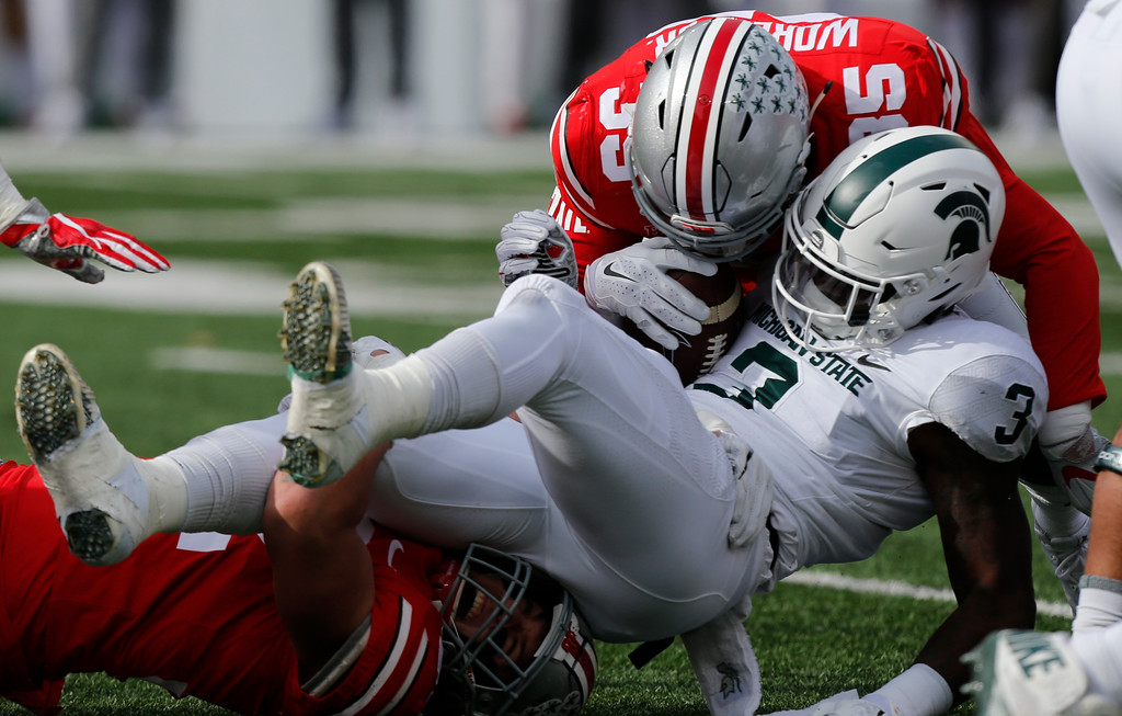 . Ohio State linebackers Tuf Borland, left, and Chris Worley tackle Michigan State running back L.J. Scott during the first half of an NCAA college football game Saturday, Nov. 11, 2017, in Columbus, Ohio. Ohio State beat Michigan State 48-3. (AP Photo/Jay LaPrete)