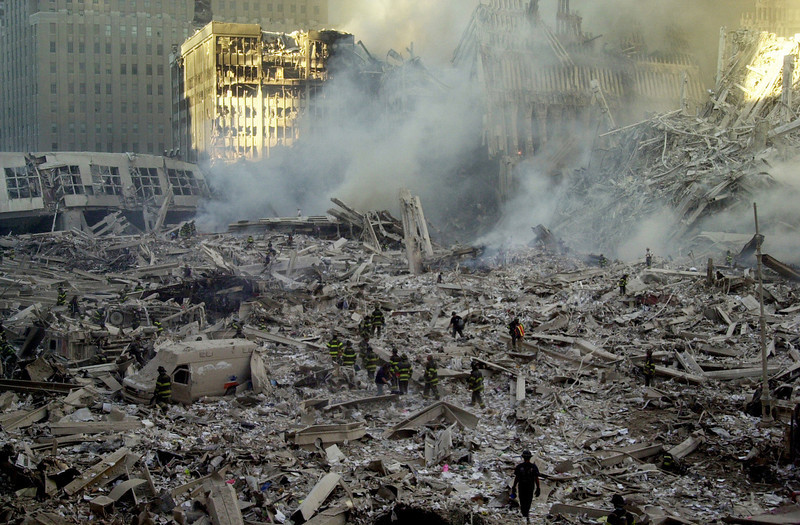 . Firefighters walk through smoldering debris at the site of the World Trade Center in New York Tuesday, Sept. 11, 2001.  (AP Photo/Graham Morrison)