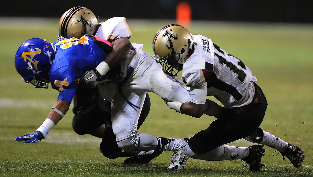 . Bishop Amat\'s Trevon Sidney is tackled by the Alemany defense in the first half of a prep football game at Bishop Amat High School in La Puente, Calif., on Friday, Oct. 25, 2013.    (Keith Birmingham Pasadena Star-News)
