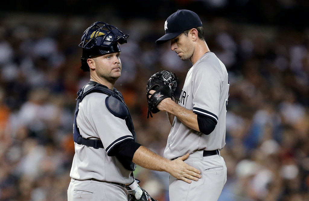 . New York Yankees catcher Brian McCann, left, talks with pitcher Brandon McCarthy after walking Detroit Tigers\' Rajai Davis with the bases loaded to score J.D. Martinez in the second inning of a baseball game in Detroit Tuesday, Aug. 26, 2014. (AP Photo/Paul Sancya)