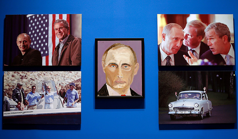 """. A portrait of Vladimir Putin, President of Russia painted by former president George W. Bush is displayed between photographs as part of the exhibit, \""""The Art of Leadership: A President\'s Personal Diplomacy\"""" at the George W. Bush Presidential Library and Museum on April 4, 2014 in Dallas, Texas. The exhibit opens to the public on April 5 and features paintings of 24 world leaders. (Photo by Stewart F. House/Getty Images)"""