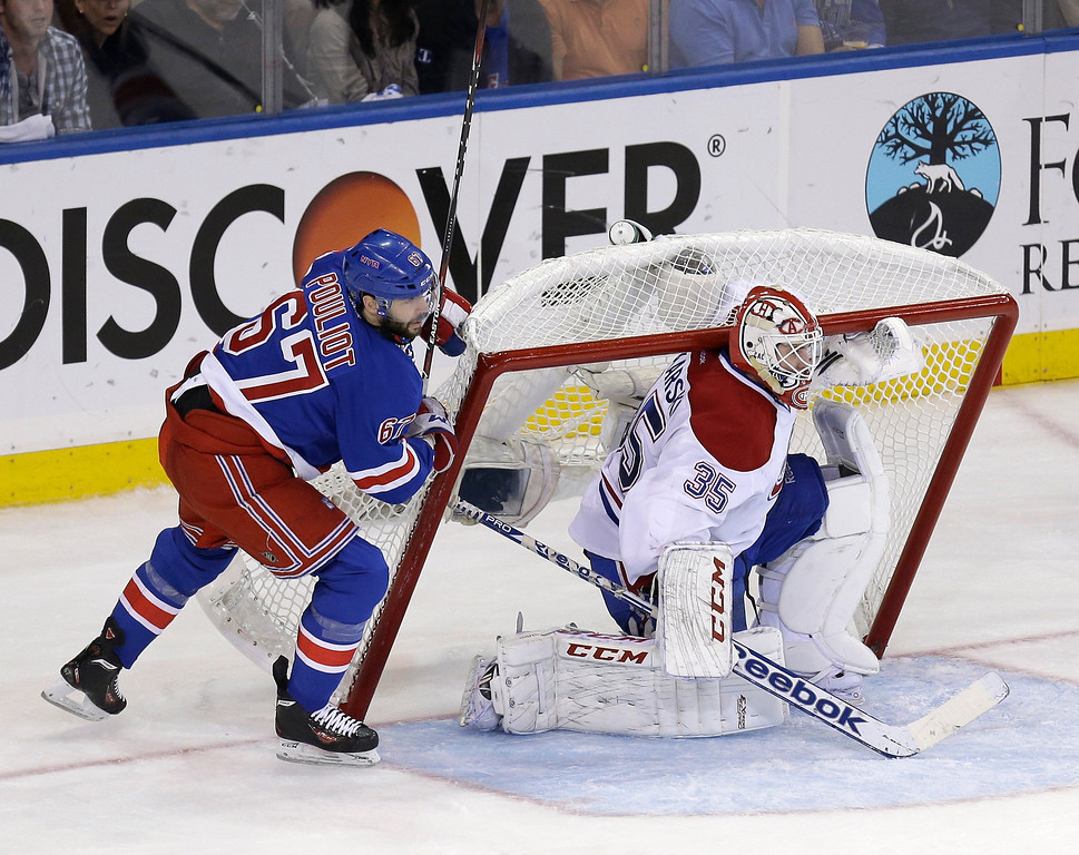 . New York Rangers\' Benoit Pouliot, left, pushes the net onto Montreal Canadiens goalie Dustin Tokarski during the second period of Game 4 of the NHL hockey Stanley Cup playoffs Eastern Conference finals, Sunday, May 25, 2014, in New York. (AP Photo/Seth Wenig)