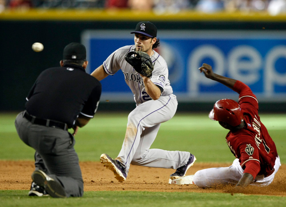 . Colorado Rockies shortstop Charlie Culberson (23) gets the force out on Arizona Diamondbacks shortstop Didi Gregorius (1) in the ninth inning during a baseball game, Sunday, Aug. 10, 2014, in Phoenix. (AP Photo/Rick Scuteri)