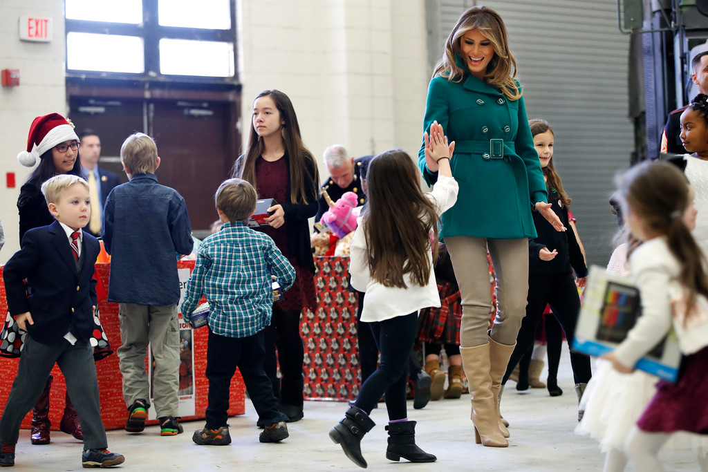 ". First lady Melania Trump high fives the daughter of a military family, Wednesday, Dec. 13, 2017, while sorting toys during a ""Toys for Tots\"" event at Joint Base Anacostia-Bolling in Washington. (AP Photo/Jacquelyn Martin)"