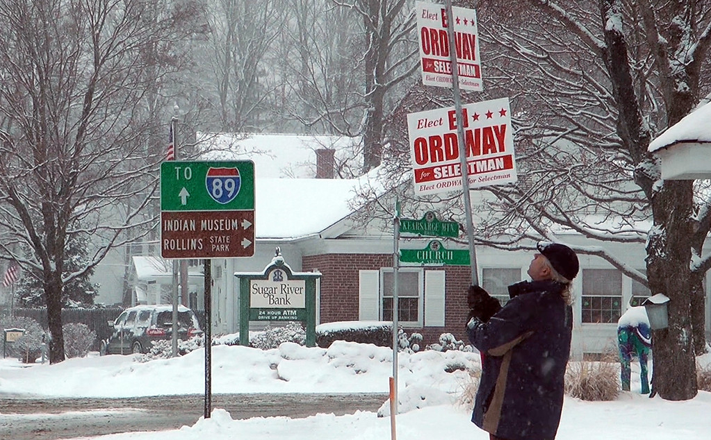 . Ed Ordway, a candidate for the Board of Selectman in Warner, N.H., holds a campaign sign outside Town Hall on Tuesday, March 13, 2018. Last year, when a storm also coincided with Town Meeting Day, nearly 80 communities postponed their elections. (AP Photo/Holly Ramer)