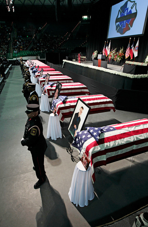 . An honor guards stand next to twelve caskets at the West Memorial Service on April 25, 2013 in Waco, Texas. (Photo by Erich Schlegel/Getty Images)