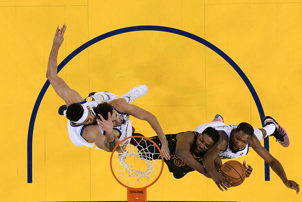 . Cleveland Cavaliers center Tristan Thompson, second from right, tries to grab the ball next to Golden State Warriors forward Kevin Durant, right, during the second half of Game 1 of basketball\'s NBA Finals in Oakland, Calif., Thursday, May 31, 2018. The Warriors won 124-114 in overtime. (Kyle Terada/Pool Photo via AP)