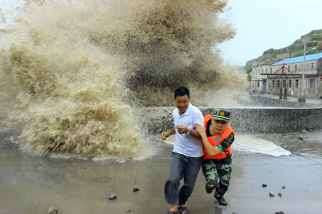 . A frontier soldier helps a man move away from waves ahead of Typhoon Soulik in Wenzhou, Zhejiang province, July 13, 2013. China braced on Friday for the impact of Typhoon Soulik as the toll of dead and missing from torrential rain across a broad swathe of China climbed beyond 200. REUTERS/China Daily
