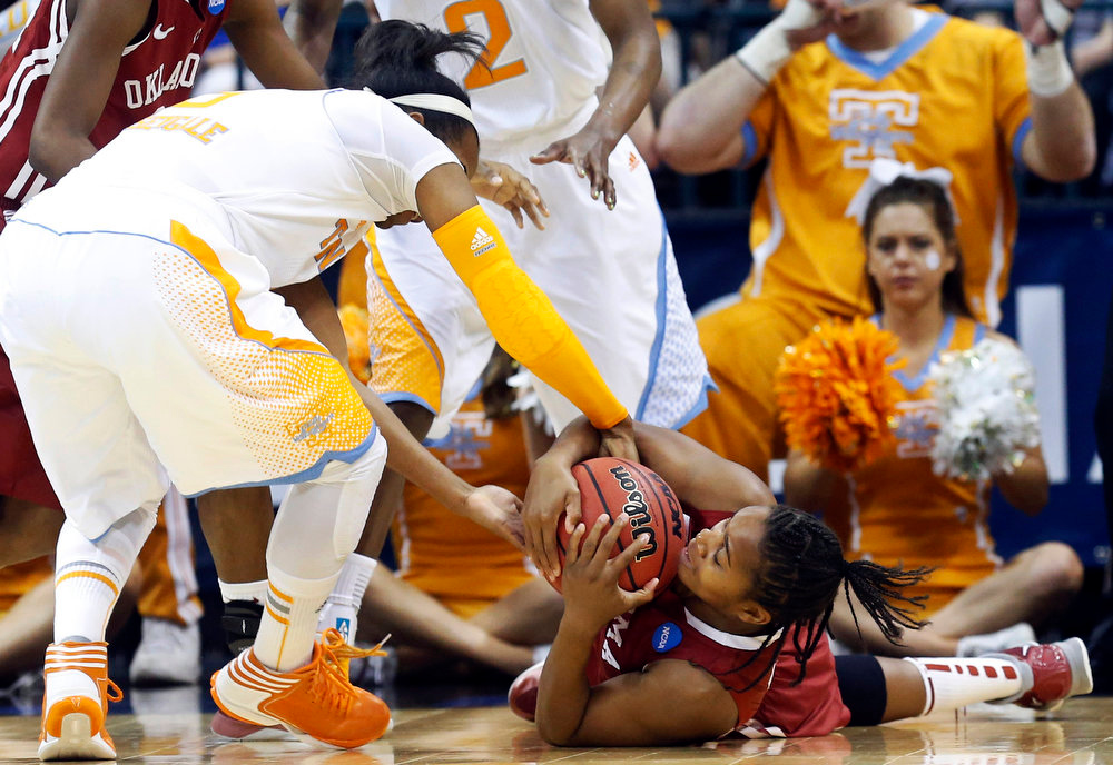 Description of . Tennessee guard Kamiko Williams, left, and Oklahoma guard Jasmine Hartman, right, fight for control on the ball in the first half of a regional semifinal in the women's NCAA college basketball tournament in Oklahoma City, Sunday, March 31, 2013. (AP Photo/Sue Ogrocki)