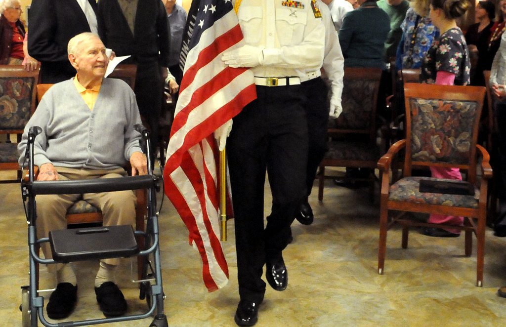 . Former Navy Capt. Charles Burrows watches as a color guard from VFW Post 10818 of New Richmond, Wis. posts the colors in his honor before the start of a medal ceremony at Red Cedar Canyon Nursing home in Hudson, Wis. on Tuesday, Feb. 25, 2014.  Burrows, 95, a Navy captain during World War II, was presented with the Navy Commendation medal, awarded for sustained acts of heroism, for his service in fourteen major naval operations aboard the battleship USS Tennessee during his four years in the South Pacific.  (Pioneer Press: John Doman)