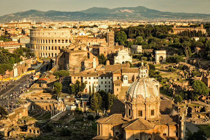 A sunrise casts golden light onto the Roman Forum and Colloseum in Rome, Italy.