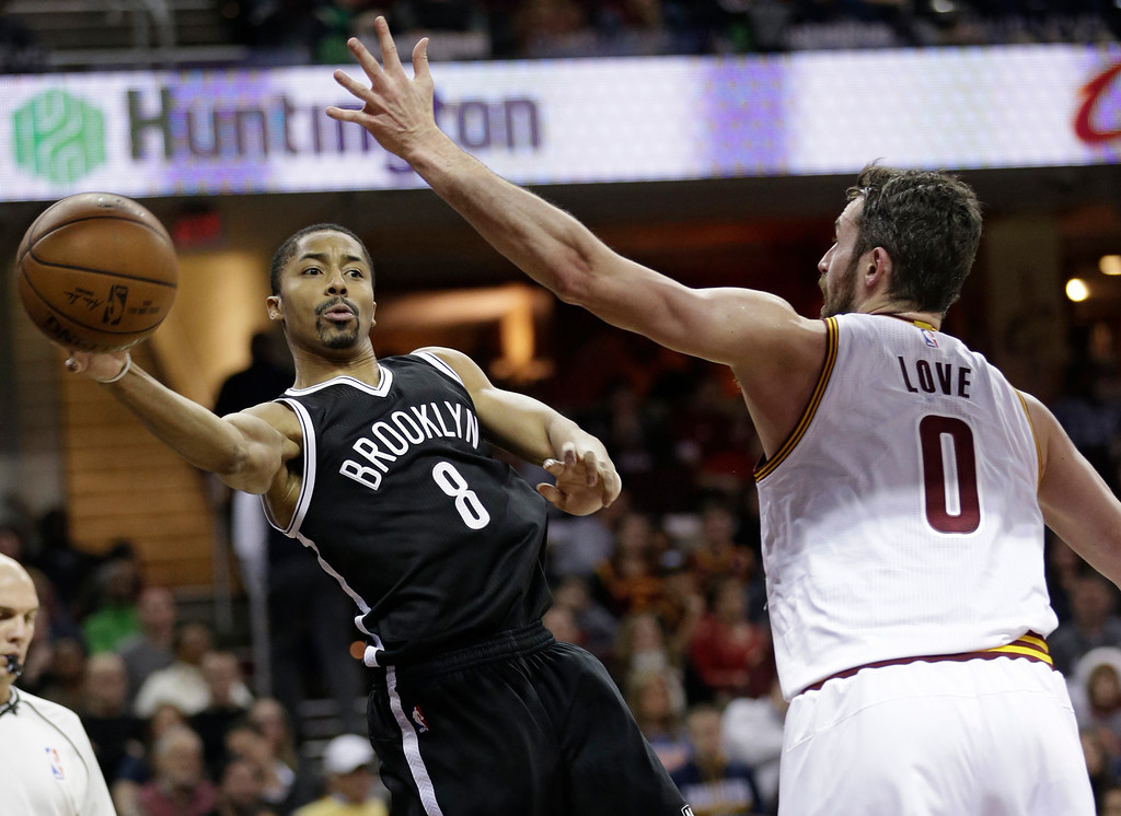 . Brooklyn Nets\' Spencer Dinwiddie (8) passes around Cleveland Cavaliers\' Kevin Love (0) in the first half of an NBA basketball game, Friday, Dec. 23, 2016, in Cleveland. (AP Photo/Tony Dejak)